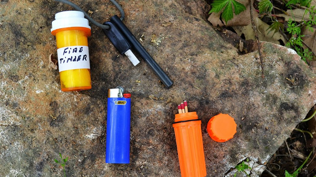 Fire can be essential to survival. The author suggests the survival kit contain three sources of fire and proven all weather tinder.