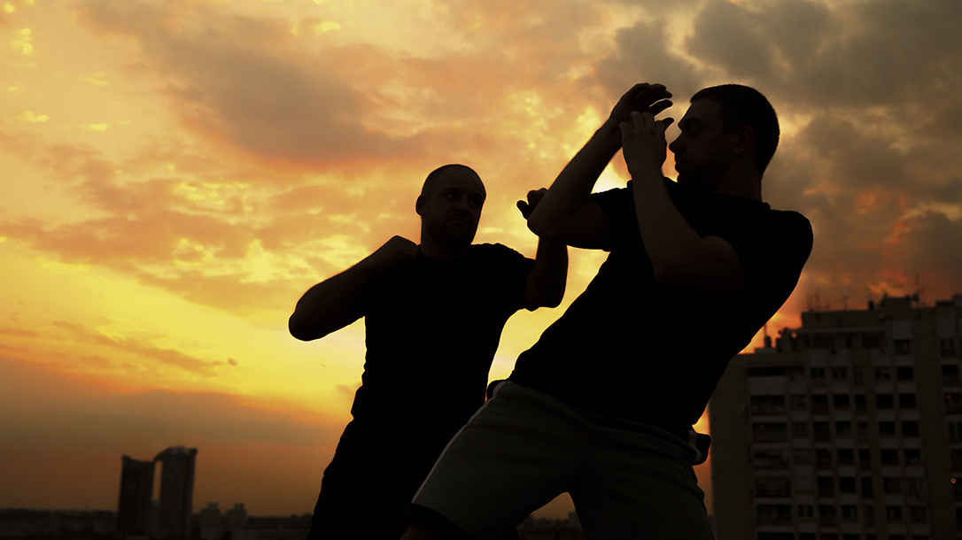Two men training on a rooftop for a fight.