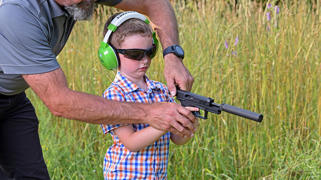 Father teaching his son how to safely handle a firearm.