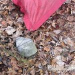 Attach the tarp to a rock or stake.
