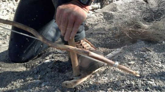 Use your foot to brace the hearth and spindle and saw to make fire.