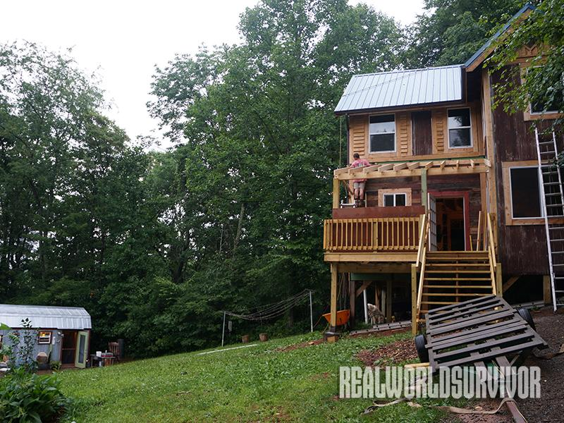 The Berzins' bigger home, overlooks their tiny house.