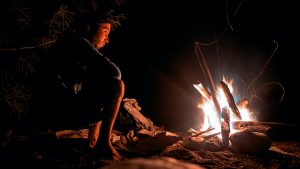 Building a fire, campfire, man sitting next to it.