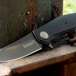 Kershaw Concierge knife, leaning against a metal post