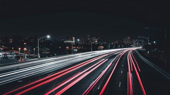 Open highway, dark city skyline