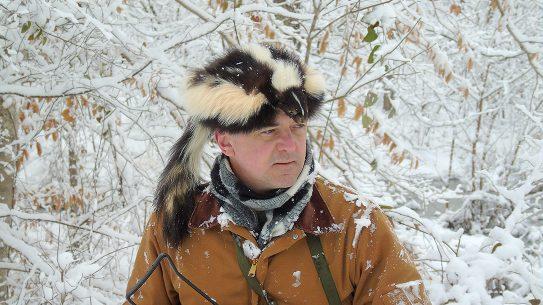 Skunk Skin Cap, man wearing the cap in snow