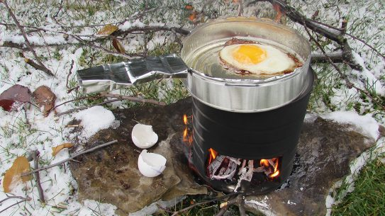 hobo stove, frying pan, cooking egg, snow, rock