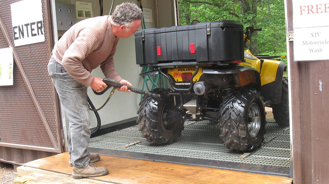 a pressure washer cleaning an ATV
