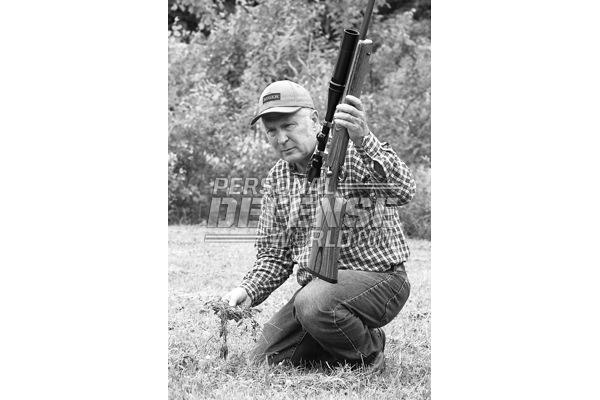 No matter what kind of hunting you do, a well sighted-in rifle is the only way to go into the field. With his Ruger Target rifle rechambered in the .220 Weatherby Rocket, the author checks for early woodchucks in the fields nearby.