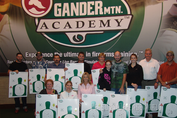 Concealed-carry students from Gander Mountain Academy stand proudly with their target results.