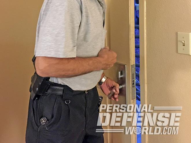 armed homeowner answering door