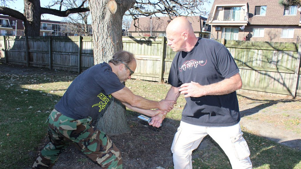 """Attack the attack. Commit and lunge your weight forward to stop the rising attack. """"C-cup"""" grab with both hands on the wrist and drop your weight into the strike."""