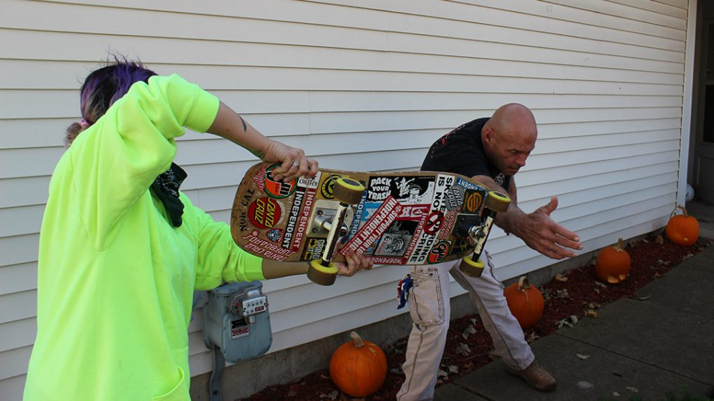 The weight of the skateboard and its metal trucks are enough to knock the knife out of her attacker's hand.
