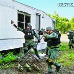 Special Response Team deputies move in to break and rake the windows of a trailer during a simulated entry.