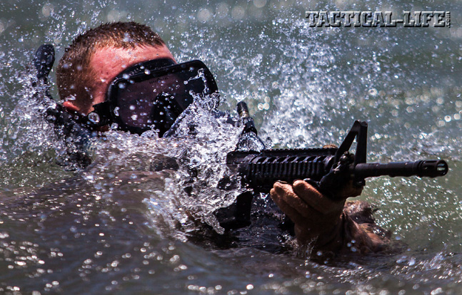 A Marine assigned to the 26th Marine Expeditionary Unit Maritime Raid Force emerges from the surf armed with a Colt M4 Carbine.