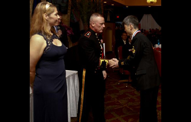 USO Okinawa Area Director, Robin Miller, left, pauses the 43rd annual USO Service Salute March 8 at the Butler Officers' Club on Camp Foster while U.S. Marine Maj. Gen. H. Stacy Clardy III, center, congratulates Japan Maritime Self-Defense Force Petty Officer 2nd Class Nobuhiko Hyakutake. Hyakutake was among seven Japan Self-Defense Force and U.S. service members recognized for volunteer efforts and community support. Hyakutake is a network engineer with the Operations Division, Naha Communications Center, JMSDF. Clardy is the commanding general of 3rd Marine Division, III Marine Expeditionary Force.