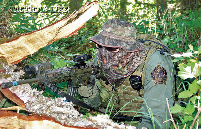 An AST SERT countersniper decked in camouflage holds a perimeter overwatch position from concealment during a day-long hostage-rescue training operation.