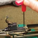SECURE IT: Tighten the front screw on the trigger until it's snug. This screw is designed to place tension on the locking pins and to remove any movement in the trigger. Put a bit of thread locker on the front screw. Then install and tighten the retaining nut.