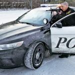 Lt. Ron Wright, armed with a Bushmaster M4, takes cover behind a Ford Taurus Police Interceptor during a felony stop.