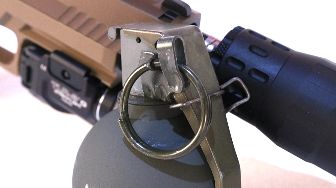 The removable wire safety clip retains the spoon in the closed potion. The safety ring must be rotated before it can be removed to arm the grenade.
