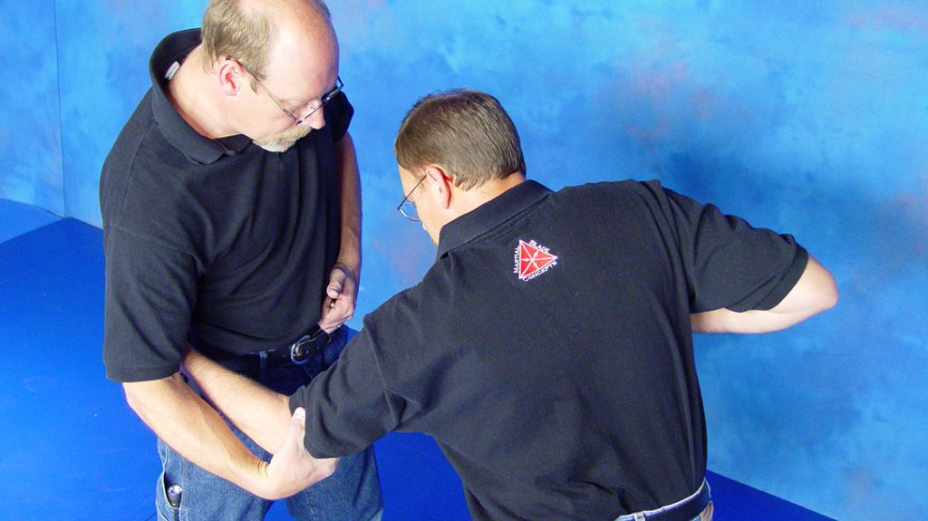 Pin the adversary's hand with your hand, turn your hips and exert further control by grasping his elbow.