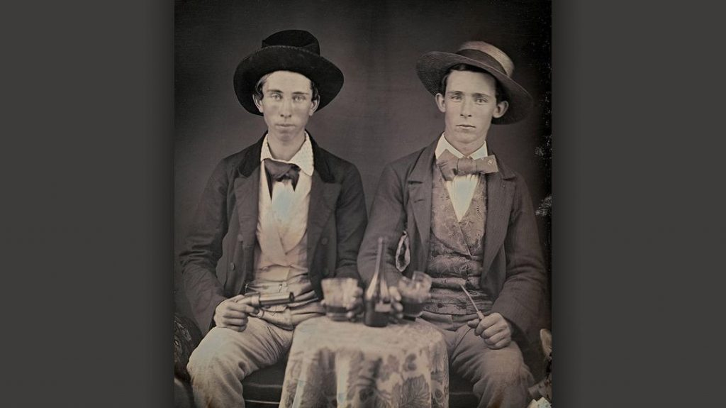 Two young men pose with a pepperbox.